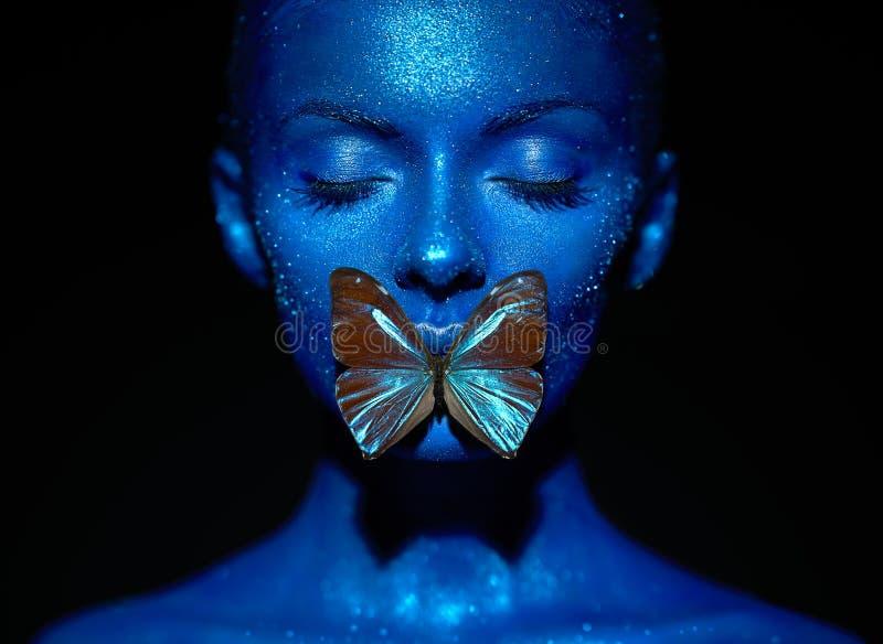 有蓝色蝴蝶的时装模特儿妇女 免版税库存图片