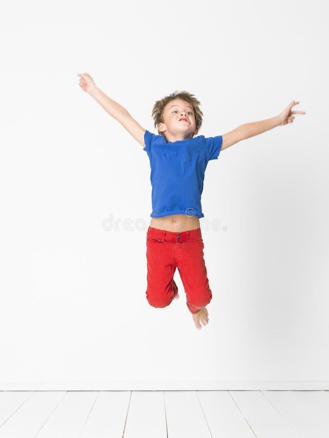 有蓝色衬衣的凉快,逗人喜爱的男孩和红色长裤是跳高在白色背景和白色木地板前面的演播室 免版税图库摄影