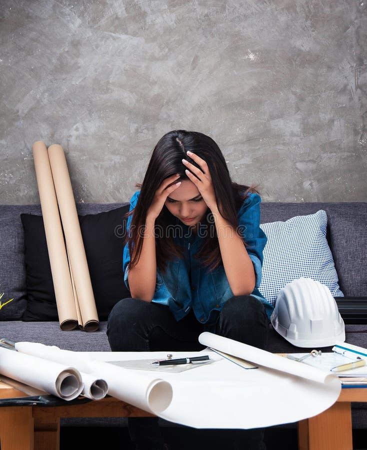 有蓝色衬衣的年轻女性建筑师研究项目,投入了她的手接触头,严肃的情感,坚苦工作 免版税图库摄影