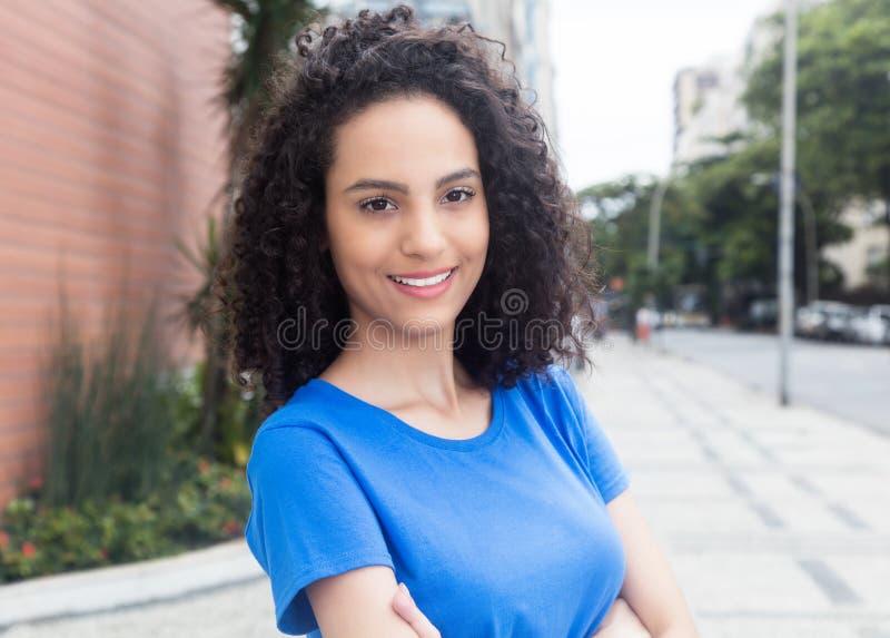 有蓝色衬衣的逗人喜爱的加勒比妇女在城市 图库摄影