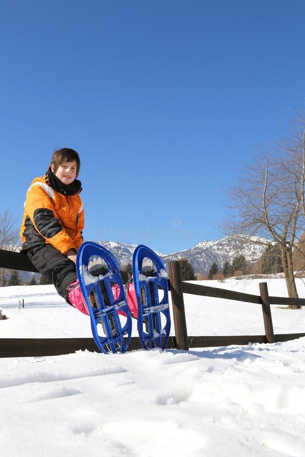 有蓝色雪靴的孩子在山 免版税图库摄影