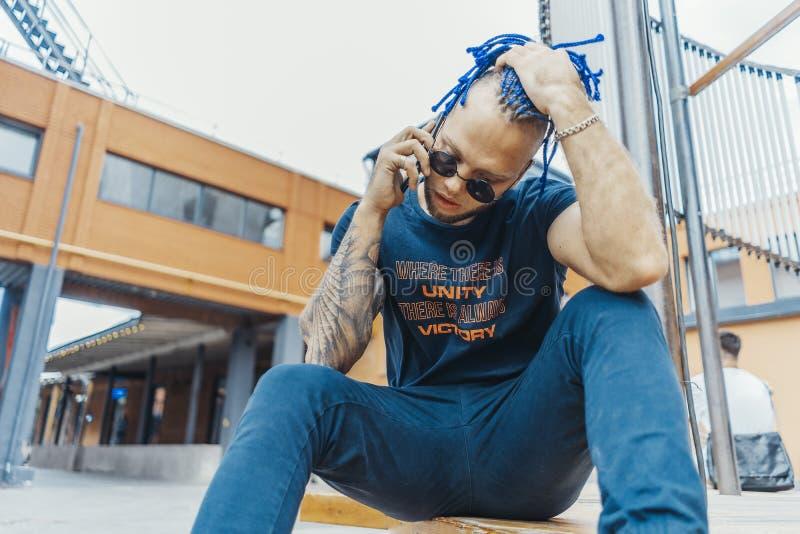 有蓝色dreadlocks的年轻可爱的人谈话由手机和接触他的头发的 免版税库存图片