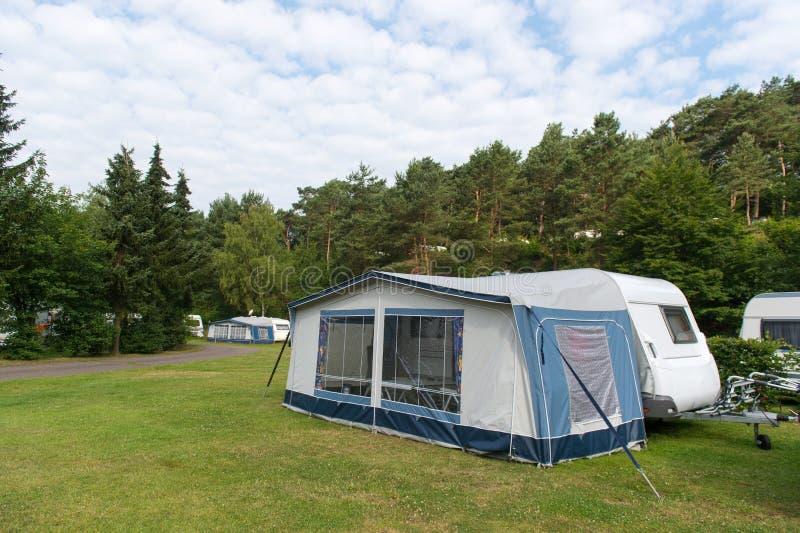 有蓬卡车和风雨棚在野营 库存图片