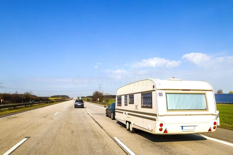 有蓬卡车或游乐车在高速公路的住房汽车拖车 免版税库存图片