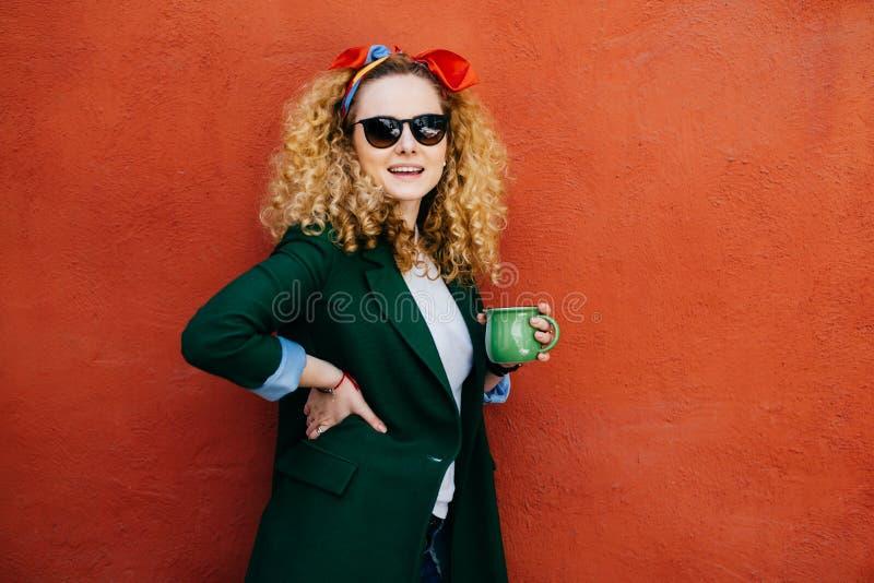 有蓬松举行在一个手杯子的金发佩带的头饰带、太阳镜和夹克的时髦年轻美丽的妇女热的咖啡 免版税库存图片