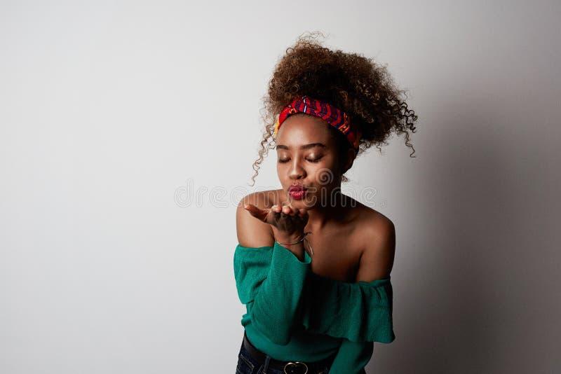 有蓬松卷发发型的,在旁边点正面可爱的年轻女性与快乐的表示,被隔绝在明亮的光 免版税库存照片