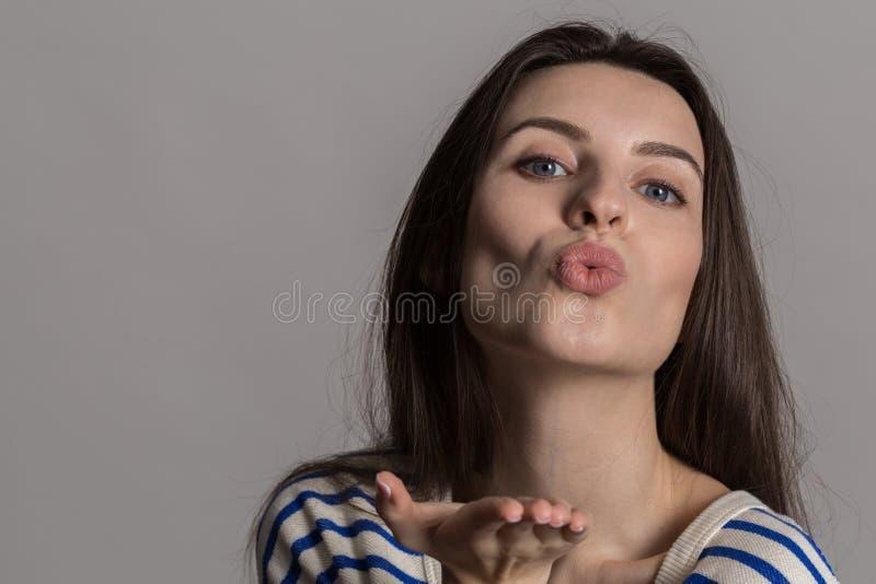 有蓬松头发的俏丽的妇女,穿戴随便对灰色演播室墙壁 库存图片