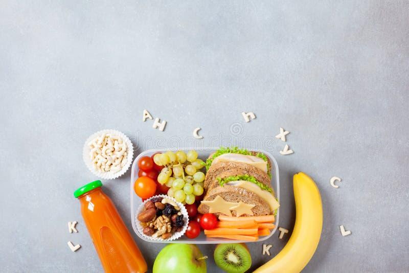 有蔬菜、水果和三明治的学校午餐箱子在厨房用桌顶视图 免版税库存照片
