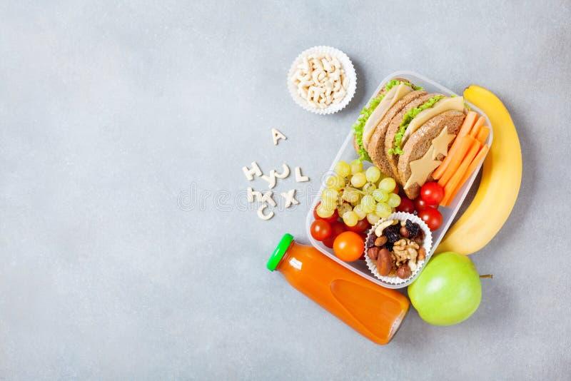 有蔬菜、水果和三明治的学校午餐箱子在台式视图 库存照片