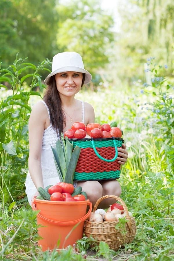 有蔬菜的妇女在庭院里 免版税图库摄影