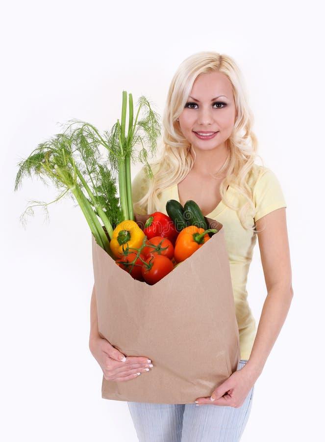 有蔬菜的白肤金发的少妇在购物袋 免版税库存图片