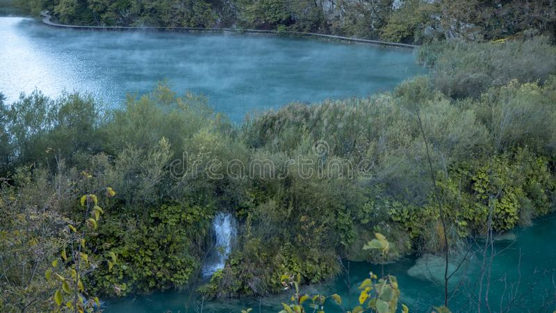 有薄雾和有雾的湖在五颜六色的Plitvice国立公园内的黎明在克罗地亚 免版税库存照片