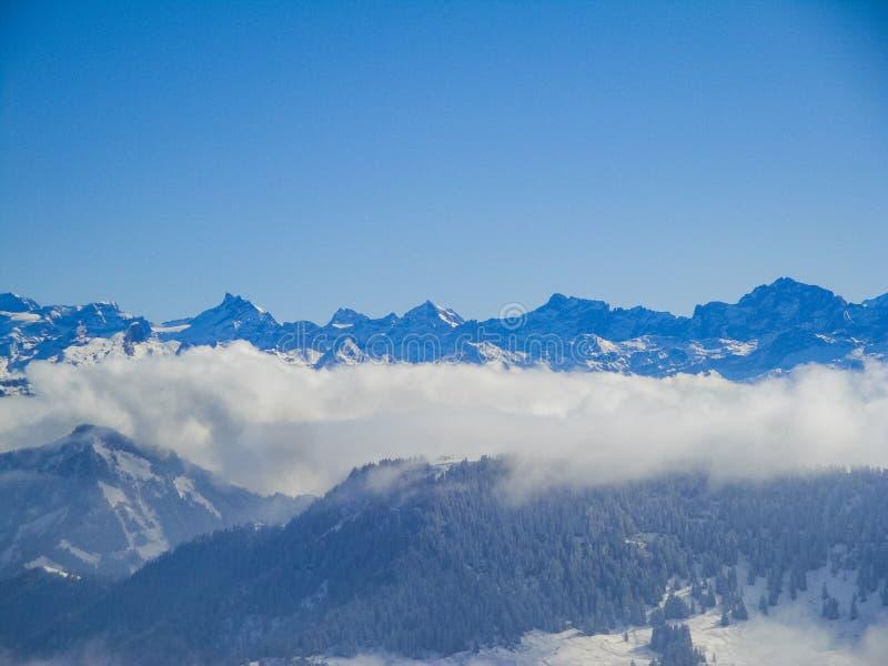 有薄雾的瑞士阿尔卑斯和云彩惊人的鸟瞰图在mou上 库存图片