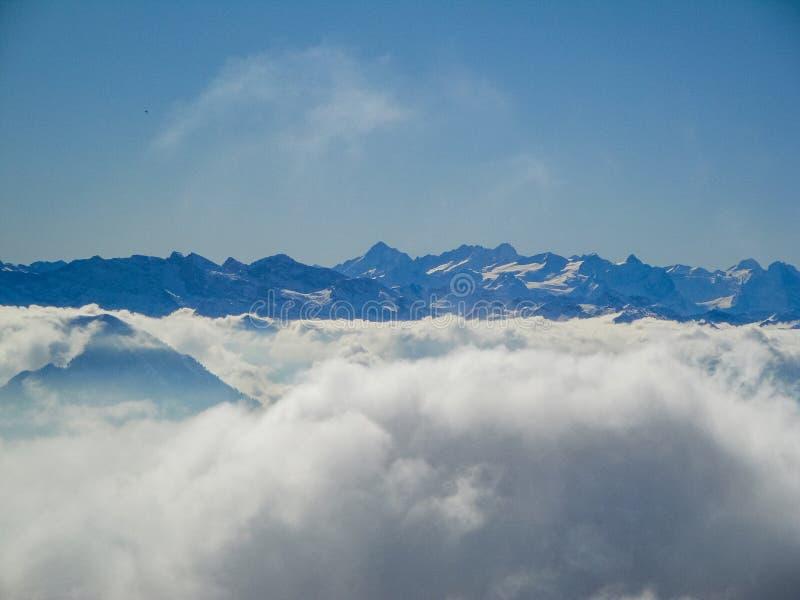 有薄雾的瑞士阿尔卑斯和云彩惊人的鸟瞰图在mou上 库存照片
