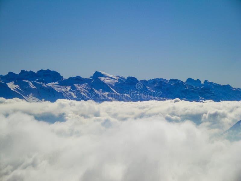 有薄雾的瑞士阿尔卑斯和云彩惊人的鸟瞰图在mou上 图库摄影