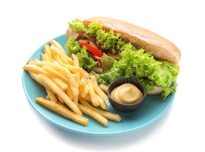 有薯条和鲜美热狗的板材在白色背景 免版税库存照片