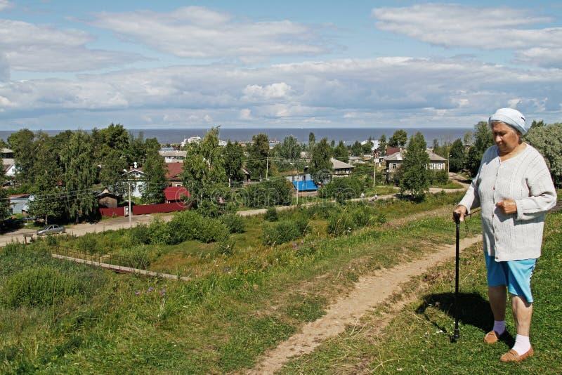 有藤茎的一名年长妇女在村庄和湖的背景站立在Belozersk 图库摄影