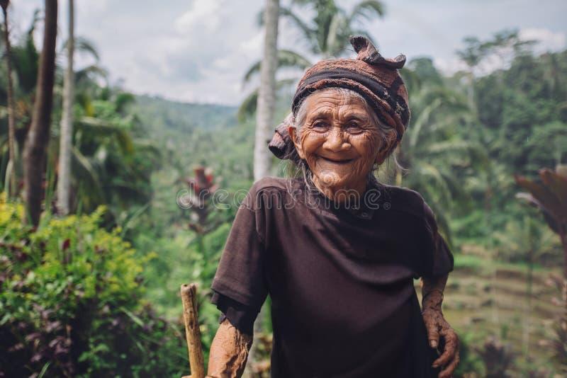 有藤茎的愉快的资深妇女在村庄 免版税库存照片