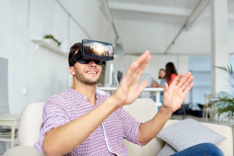 有虚拟现实耳机的愉快的人在办公室 库存图片