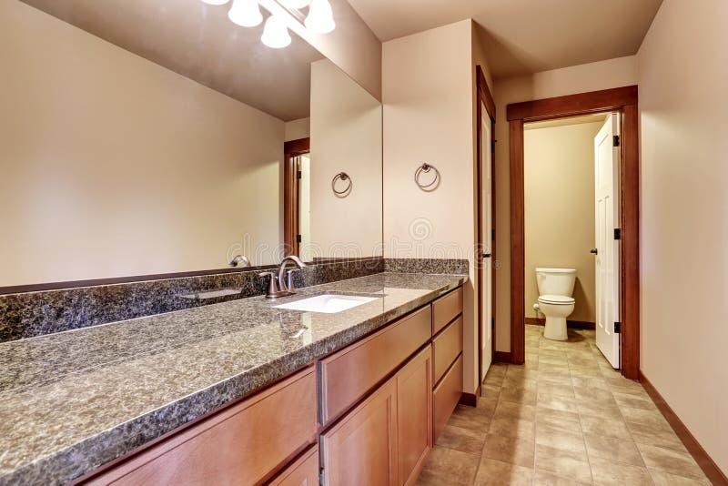 有虚荣内阁的豪华卫生间有花岗岩桌面和大镜子的 库存图片