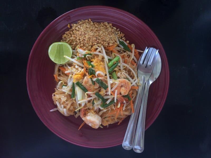 有虾或泰国电话垫泰语的炒米棍子在有叉子和匙子的板材 库存图片