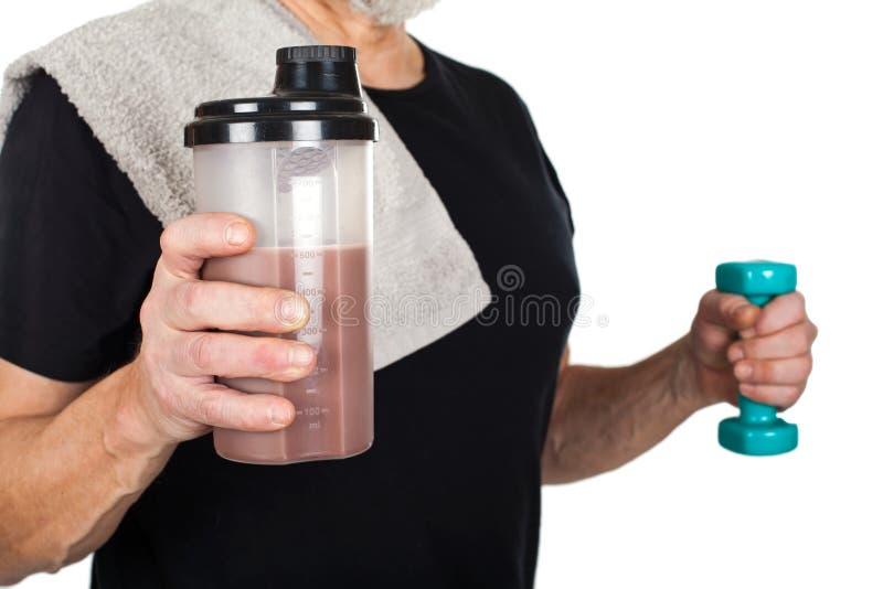 有蛋白质震动和哑铃的成熟人 免版税库存图片