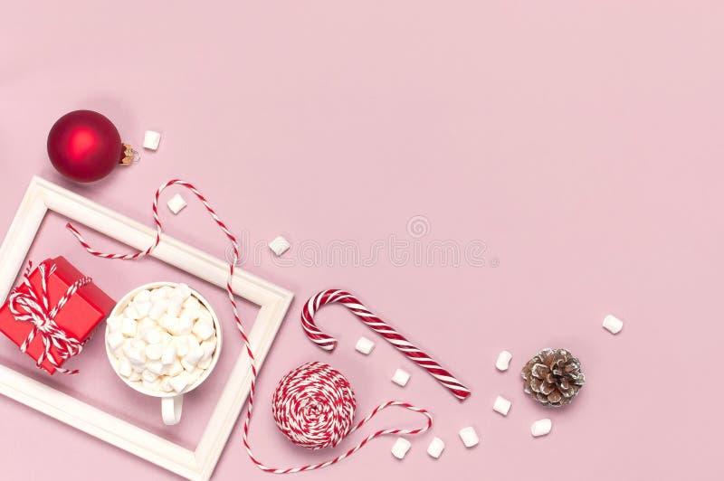 有蛋白软糖棒棒糖礼物盒红色球包装的鞋带相框的白色杯子在桃红色背景顶视图平的被放置的冬天 免版税库存照片