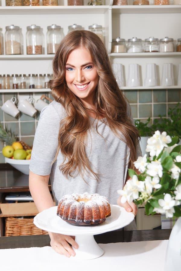 有蛋糕的愉快的俏丽的妇女 免版税库存图片