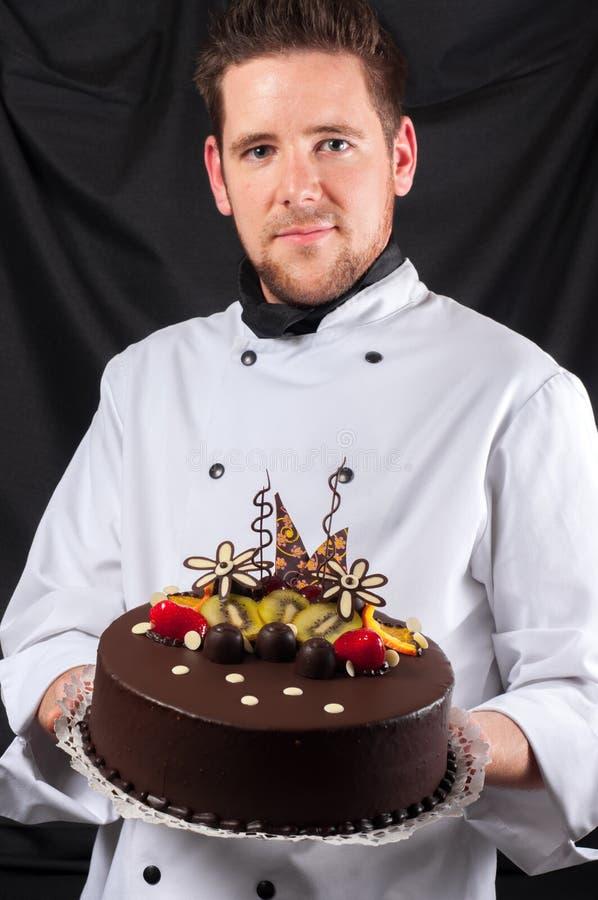 有蛋糕的英俊的主厨 免版税库存图片