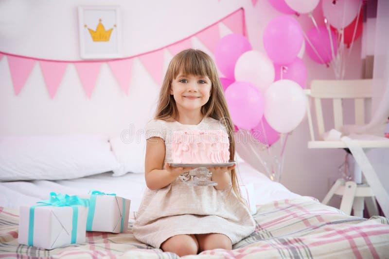 有蛋糕的逗人喜爱的女孩坐床在为生日聚会装饰的屋子里 免版税图库摄影