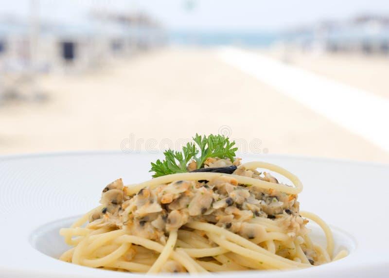 有蛤蜊的意粉在海滩的午餐的 免版税库存照片