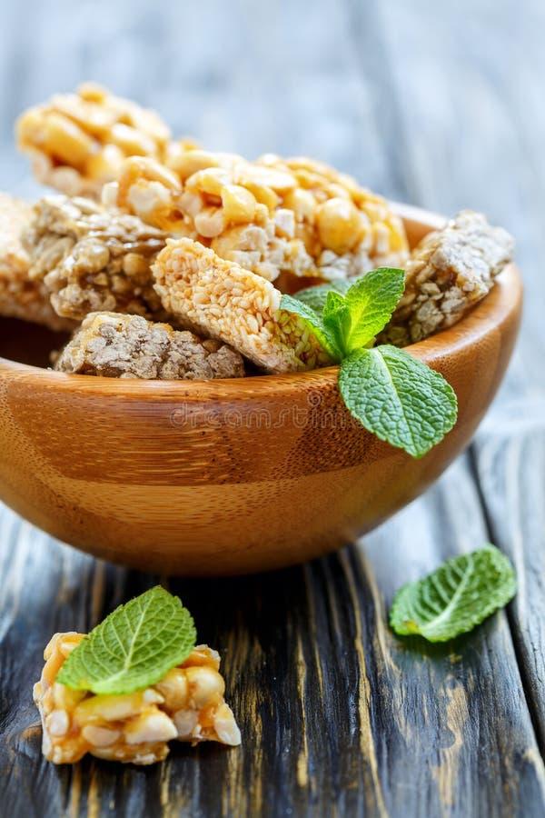 有蜂蜜酒吧的木碗用花生、芝麻籽和sunfl 免版税图库摄影