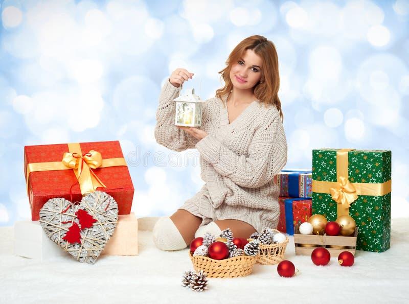 有蜡烛灯笼和礼物盒的美丽的女孩 免版税库存图片
