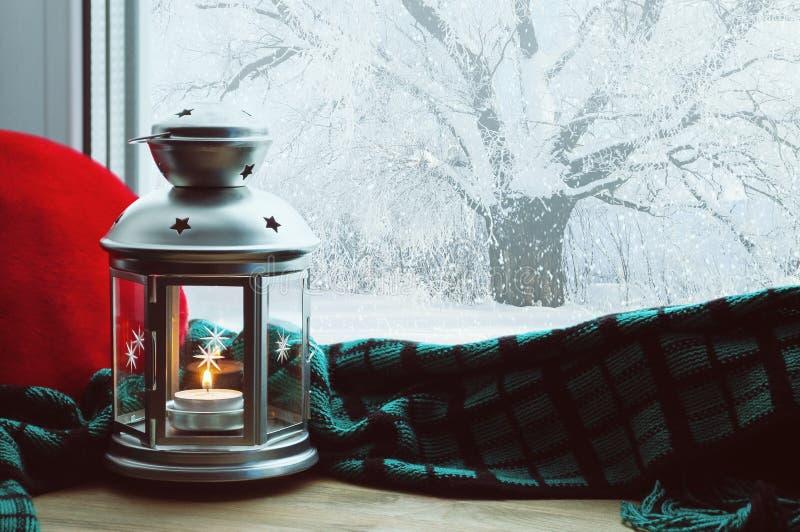 有蜡烛的冬天有枕头的背景灯笼和格子花呢披肩在户外窗台和冬天场面 免版税库存图片