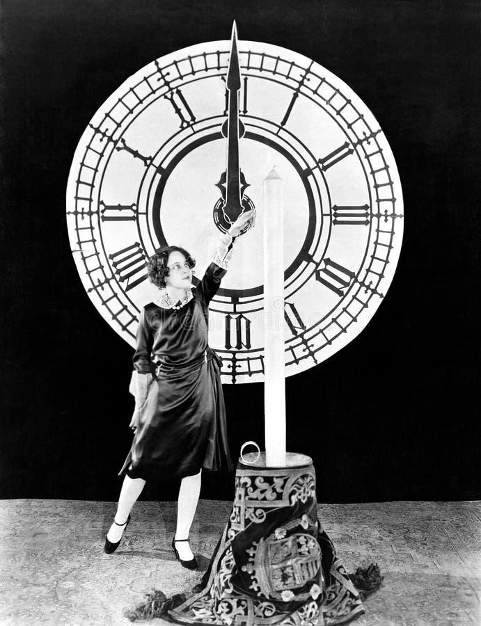 有蜡烛的妇女和时钟在除夕 免版税库存照片