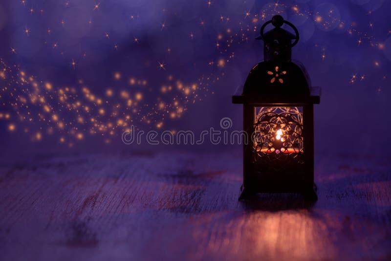 有蜡烛的灯笼在与星的美好的蓝色背景 抽象空白背景圣诞节黑暗的装饰设计模式红色的星形 库存图片