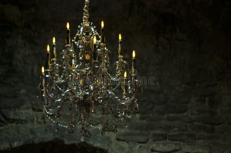 有蜡烛的老水晶枝形吊灯在黑暗的土牢 砖老墙壁 免版税库存照片