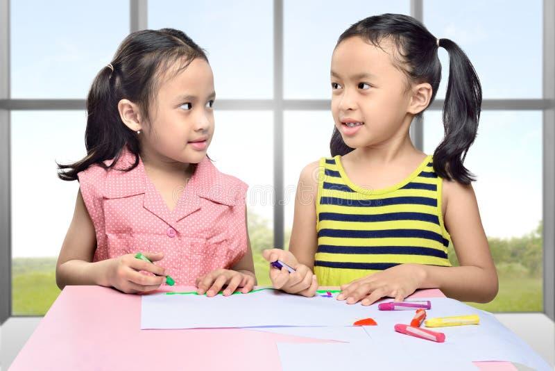 有蜡笔的微笑的两个亚洲人女孩学会画 库存图片