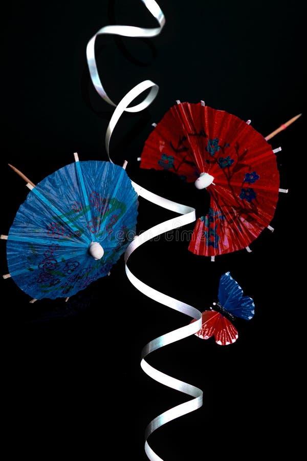 有蝴蝶和丝带的红色和蓝色鸡尾酒伞 免版税库存照片