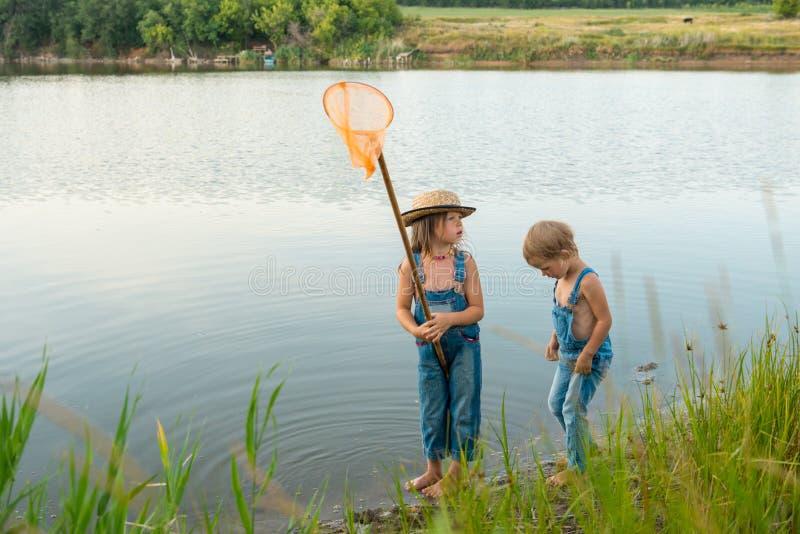 有蝴蝶网的两个孩子在河附近 图库摄影