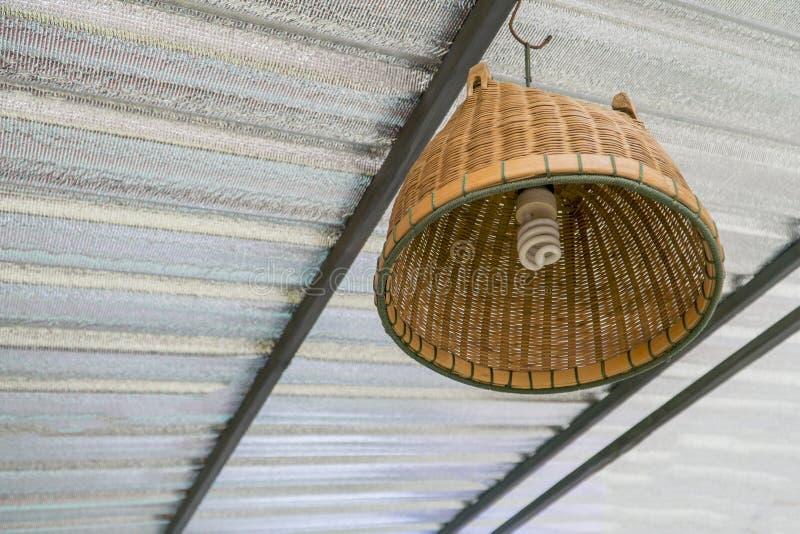 有螺旋电灯泡灯的竹灯在屋顶下 库存照片
