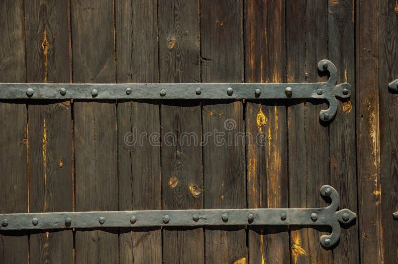 有螺柱的锻铁铰链在一个老木门 免版税库存照片