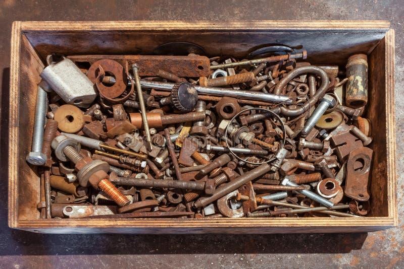 有螺栓的,螺丝,坚果,轴承,阀门,洗衣机,在金属背景的钉子木箱 免版税库存照片