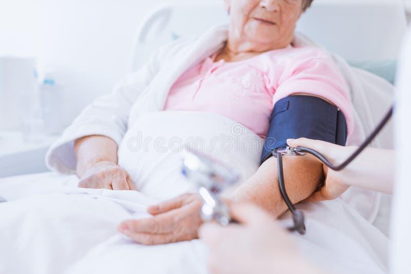 有血压显示器的资深妇女在她的胳膊和年轻实习生医院的 免版税图库摄影