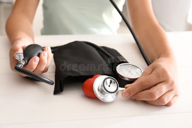 有血压计、听诊器和红心的妇女在白色桌上 库存图片