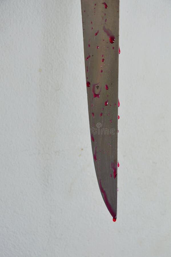 有血液的刀片在老白色大厦墙壁上 免版税库存图片