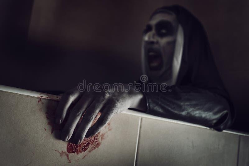 有血液的惊恐邪恶的尼姑在她的手上 图库摄影