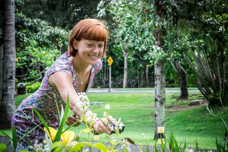 有行动照相机射击蝴蝶的年轻性感的妇女在植物中 努沙Dua公园,热带海岛巴厘岛,印度尼西亚 库存照片