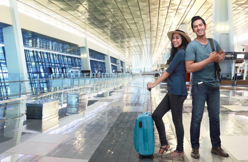 有行李等待的飞行的年轻亚裔夫妇游人 免版税库存照片