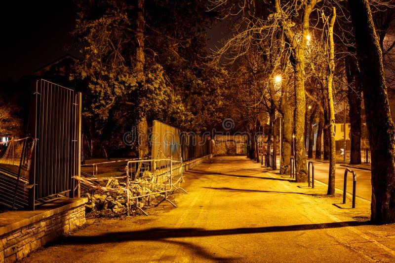 有街灯的一条偏僻的路在与篱芭障碍的晚上在意大利村庄在晚上 库存图片
